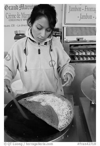 Woman preparing a crepe with cheese. Paris, France (black and white)