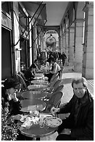 Couple eating at an outdoor table in the Palais Royal arcades. Paris, France (black and white)