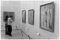 Visitors looking at Monet's Rouen Cathedral, Orsay Museum. Paris, France (black and white)