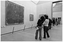 Visitors looking at a large impressionist painting of a lilly pond. Paris, France (black and white)