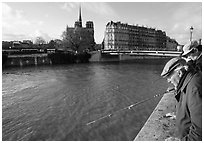 Fishermen on ile Saint Louis, with ile de la Cite in the background. Paris, France (black and white)