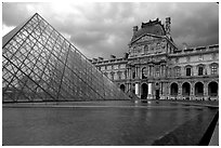 Pyramid and Richelieu wing of the Louvre under dark clouds. Paris, France (black and white)