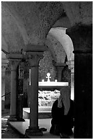 Nun in prayer in the Crypte of the Romanesque church of Vezelay. Burgundy, France (black and white)