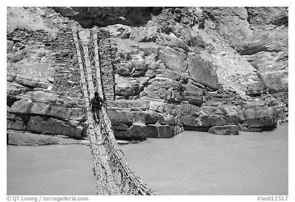 Man crossing a river by rope bridge, Zanskar, Jammu and Kashmir. India (black and white)