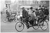 Cycle-rickshaw with a load of ten schoolchildren. New Delhi, India (black and white)