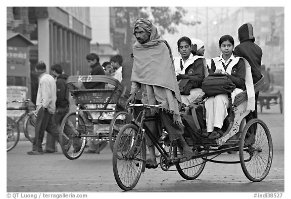 Cycle-rickshaw carrying uniformed schoolgirls. New Delhi, India (black and white)