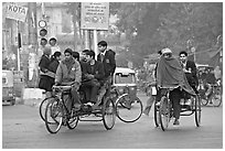 Cycle-rickshaws carrying uniformed schoolchildren. New Delhi, India (black and white)