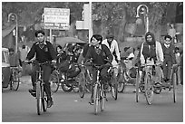 Children riding bikes in rickshaws on way to school. New Delhi, India (black and white)