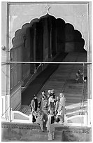 Women standing beneath arched entrance of prayer hall, Jama Masjid. New Delhi, India ( black and white)
