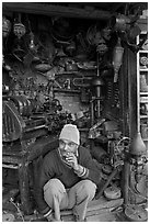 Man sitting in front of machine parts shop, Old Delhi. New Delhi, India (black and white)
