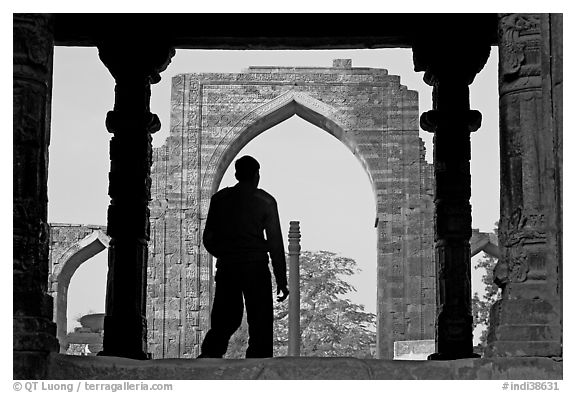 Man at entrance of ruined Quwwat-ul-Islam mosque. New Delhi, India (black and white)