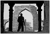 Man at entrance of ruined Quwwat-ul-Islam mosque. New Delhi, India ( black and white)