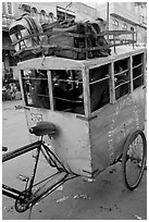 Schoolchildren in an enclosed  box towed by cycle. New Delhi, India (black and white)