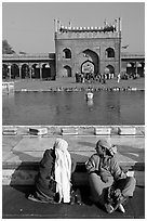 Women sitting near basin in courtyard of Jama Masjid. New Delhi, India ( black and white)