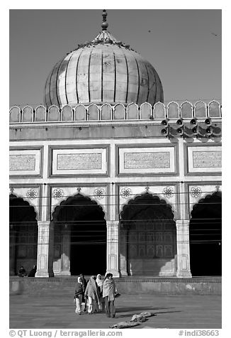 Group of people walking out of prayer hall. New Delhi, India (black and white)