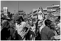 Groom covered in flowers and riding horse during Muslim wedding. Jodhpur, Rajasthan, India (black and white)