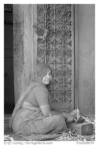 Woman in orange sari sitting next to green door and blue wall. Jodhpur, Rajasthan, India (black and white)