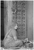 Woman in orange sari sitting next to green door and blue wall. Jodhpur, Rajasthan, India ( black and white)
