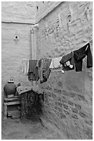 Laundry in alley with whitewashed walls tinted indigo. Jodhpur, Rajasthan, India (black and white)