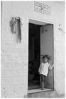 Young boy in doorway of house painted light blue. Jodhpur, Rajasthan, India ( black and white)