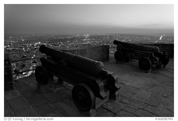Cannons on top of Mehrangarh Fort, and city lights and dusk. Jodhpur, Rajasthan, India (black and white)