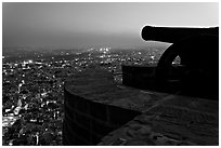 Cannon on top of Mehrangarh Fort, and city lights below. Jodhpur, Rajasthan, India (black and white)