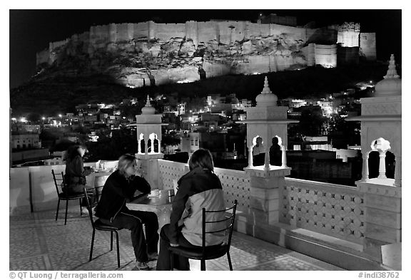 Travelers on rooftop terrace with view of Mehrangarh Fort by night. Jodhpur, Rajasthan, India (black and white)