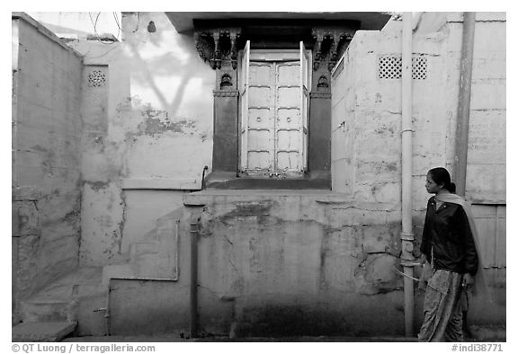 Woman walks infront of blue tinted whitewashed wall. Jodhpur, Rajasthan, India (black and white)