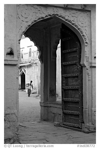Archway with woman carrying water in courtyard. Jodhpur, Rajasthan, India (black and white)