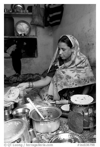 Woman with headscarf stacking chapati bread. Jodhpur, Rajasthan, India (black and white)