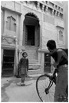 Boy on bicycle looking at girl in front of blue house. Jodhpur, Rajasthan, India (black and white)