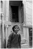 Schoolgirl standing in front of a house with blue tint. Jodhpur, Rajasthan, India (black and white)