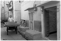 Man with vegetables car in front of painted house. Jodhpur, Rajasthan, India (black and white)