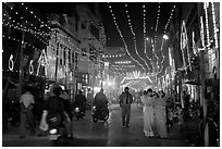 Women walking in street with illuminations. Varanasi, Uttar Pradesh, India (black and white)