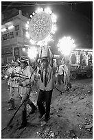 Uniformed musicians and men carrying lights during wedding procession. Varanasi, Uttar Pradesh, India (black and white)