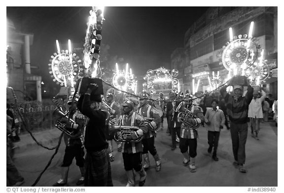 Musicians, men carrying lights, and carriage during wedding procession. Varanasi, Uttar Pradesh, India (black and white)