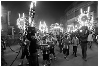 Musicians, men carrying lights, and carriage during wedding procession. Varanasi, Uttar Pradesh, India ( black and white)