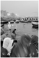 Women on the banks of the Ganga River in rosy dawn light. Varanasi, Uttar Pradesh, India (black and white)