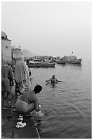 Hindu men dipping in the Ganges River at dawn. Varanasi, Uttar Pradesh, India (black and white)