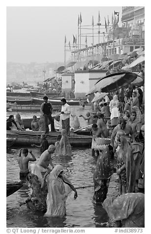 Women standing in Ganga River at sunrise, Dasaswamedh Ghat. Varanasi, Uttar Pradesh, India (black and white)