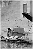 Man sitting near unbrella. Varanasi, Uttar Pradesh, India (black and white)
