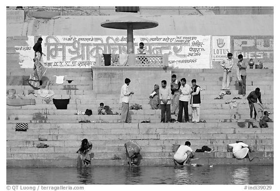 People washing cloths, steps, and Indi inscriptions. Varanasi, Uttar Pradesh, India (black and white)