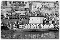 Boat packed with men near Dasaswamedh Ghat. Varanasi, Uttar Pradesh, India (black and white)