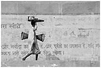 Man carrying a plater in front of wall with inscriptions in Hindi. Varanasi, Uttar Pradesh, India (black and white)
