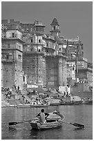 Man rowing boat beneath Munshi Ghat. Varanasi, Uttar Pradesh, India ( black and white)