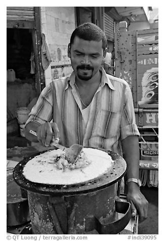 Man preparing breakfast dosa, Colaba Market. Mumbai, Maharashtra, India (black and white)
