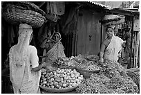 Women with baskets on head buying vegetables, Colaba Market. Mumbai, Maharashtra, India (black and white)