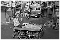 Vegetable vendor pushing cart with truck in background, Colaba Market. Mumbai, Maharashtra, India (black and white)