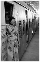 Woman standing at door of suburban train. Mumbai, Maharashtra, India ( black and white)