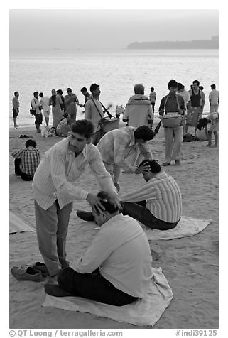 Head rub given by malish-wallah, Chowpatty Beach. Mumbai, Maharashtra, India (black and white)